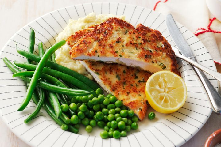 Chicken schnitzel with cheesy mash, beans and peas